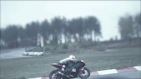 Bagni il giro della bici nera su una pista piovosa di moto video d archivio