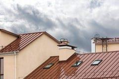 Bagni il tetto rosso del metallo con i lucernari durante la pioggia fotografia stock libera da diritti