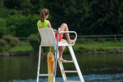 Bagnino che si siede sulla sedia davanti al lago sulla vista posteriore Immagini Stock