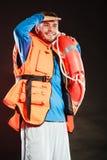 Bagnino in maglia di vita con il salvagente della boa di anello Fotografie Stock