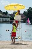 Bagnino sulla sedia con l'ombrello davanti al lago Fotografie Stock Libere da Diritti