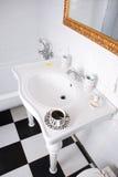 Bagno bianco con la tazza di caffè su un lavandino immagini stock