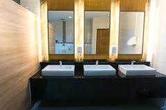 Bagno commerciale con il lavandino tre e lo specchio Immagine Stock