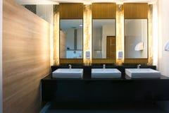 Bagno commerciale con il lavandino tre e lo specchio Fotografia Stock
