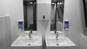 Bagno con i lavandini, sapone, acqua di rubinetto Fotografie Stock