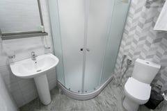 Bagno, con le mattonelle ed i colori luminosi della scopa, doccia con le porte glassate, specchio sopra il lavandino Appendendo u fotografia stock