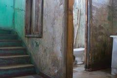 Bagno consumato vicino ad una scala decomposta in costruzione condannata Fotografie Stock