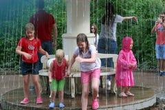 Bagno dei bambini sotto l'acqua della fontana Immagini Stock