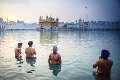 Bagno sikh degli uomini nel lago santo al tempio dorato Immagine Stock