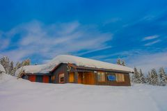 Bagnsasen, Norway - April, 02, 2018: Outdoor view of lonely wooden modern house covered with heavy snow. In Bagnsasen region in Norway Stock Images