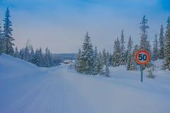 Bagnsasen Norwegia, Kwiecień, -, 02, 2018: Plenerowy widok znak uliczny prędkości ograniczenie przy jeden stroną podczas zimy w d Obrazy Stock