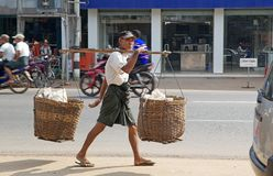 Bago. Burmese man in traditional clothes is carrying goods along the street in Bago, Myanmar. Bago is a city and capital of Bagon Region. It is located 80 km royalty free stock image