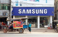 Bago. Burmese woman in traditional dress is getting out from a traditional local share taxi in Bago, Myanmar in front of Samsung shop. Bago is a city and capital royalty free stock photography