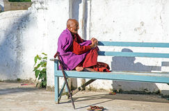 BAGO, MYANMAR - November 24, 2015: Old monk enjoying the sun in Stock Photography