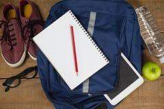 Bagpack、日志、鞋子、眼镜、数字式片剂、苹果和水瓶 库存照片