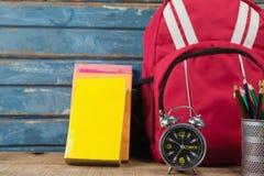 Bagpack, libri, sveglia e supporto della penna Immagini Stock