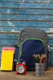 Bagpack, libri, sveglia e supporto della penna Fotografia Stock