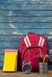 Bagpack, libri, sveglia e supporto della penna Fotografie Stock Libere da Diritti