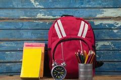 Bagpack, libri, sveglia e supporto della penna Immagine Stock