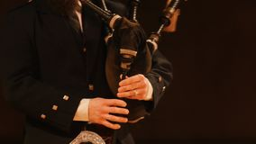 Bagpipe player plays musical instrument at the stage. Close up stock footage