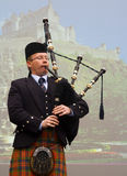 Bagpiper. In kilt with Edinburgh Castle in background stock image