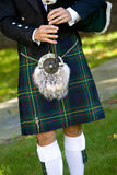Bagpiper. Scottish bagpiper playing bagpipes. This is a detail shot of a man wearing a kilt stock photography