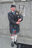 Bagpiper blowing his pipes, Edinburgh Royalty Free Stock Images