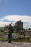 A bagpiper in front of Eilean Danon Castle Stock Images