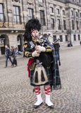 Bagpiper with his bagpipe in the square. Nearby are walking tou Stock Photos