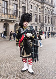 Bagpiper with his bagpipe in the square. Nearby are walking tour Stock Photos
