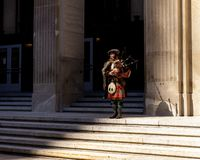Bagpiper performing on building steps stock images