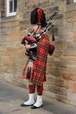 The street bagpiper in the city Edinburgh in Scotland. The bagpiper is playing in one of the streets, Royal Mile in the city Edinburgh in Scotland in the summer Stock Photos