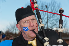 Bagpiper plays as he is walking. Made, North-Brabant, Netherlands – February 19, 2012 – Carnival Parade, impression of the people, bagpiper plays and looks Royalty Free Stock Photo