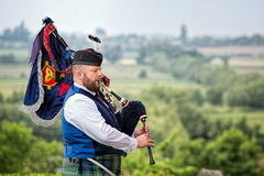 Bagpiper plays bagpipes overlooking landscape. Royalty Free Stock Images