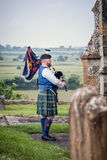Bagpiper plays in churchyard overlooking landscape. Royalty Free Stock Photos