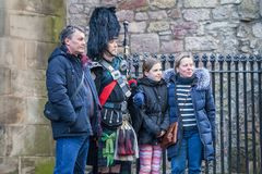 Bagpiper on streets of Edinburgh. Edinburgh, Scotland, February 10, 2018: Bagpiper on streets of Edinburgh. Tourists taking a picture with a bagpiper royalty free stock images
