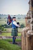 Bagpiper sztuki w churchyard przegapia krajobraz Zdjęcia Royalty Free