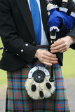 Bagpipes and Sporran. Close up of scottish piper's hands showing bag, chanter, kilt and sporran royalty free stock photography