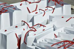 Bags. Many white paper bags with red string handles Stock Photo