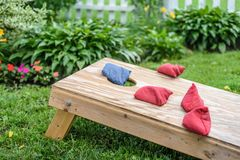 Playing bags corn hole game in backyard. Bags in air landing on cornhole board in grass in backyard royalty free stock photography