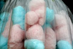 Bags of candy floss. Pink and blue candy floss hang from the stall at the fun fair, it is sweet and delicious for both children and adults alike Royalty Free Stock Photography