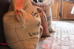 Bags of coffee beans. On the brick floor, against the background of a wooden door Stock Photo