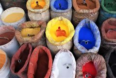 Bags of color. Various plastic bags and pails hold brightly colored solid powder ink paint for distribution with multicolored scoops Stock Photo