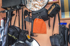 Bags, covers and reflectors for photos. Collection of different tripods for cameras and reflector by the window Stock Photography