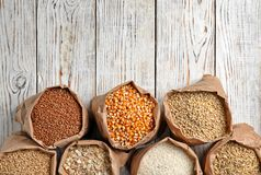 Bags of different cereal grains. On wooden background, flat lay composition with space for text stock image