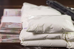Bags of drugs, pistol and money on table Royalty Free Stock Images