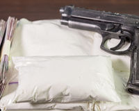 Bags of drugs, pistol and money on table Royalty Free Stock Photo