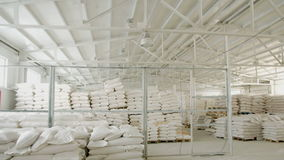 Bags with flour in warehouse of flour factory. Flour stock. Mill warehouse