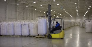 Bags handling to stacking in warehouse by forklift. Forklift with a big bag. Yellow forklift in distribution warehouse