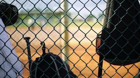 Bags hanging from fence inside dugout at baseball field stock video